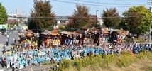 毎年11月第2週の土日に東村山市役所周辺で開催される市民産業祭。お祭り2日目の日曜日には、市内各地から山車が集結します。山車の見比べや、祭囃子の聞き比べが一挙にできる絶好の機会です。この写真は東村山市祭囃子保存連合協議会の設立五十周年記念誌用の記念写真を撮影するために、集結したものです。