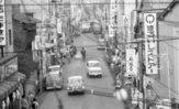 府中街道側から、北東の久米川駅の方に向かって撮影。今と違って歩道がなく、通っている自家用車やバスも、現在とはフォルムが大きく異なっているのがわかります。